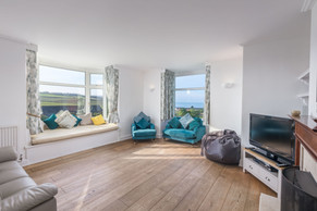 The large living room comes with a pretty window seat for soaking up the views
