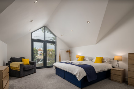 Large bedroom with bed and armchair by full height window