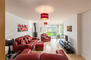 Large sitting room with bright, sink-into red sofas