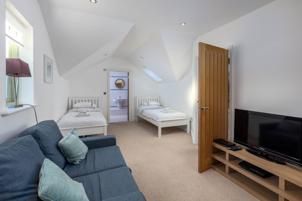 A light and airy twin room complete with sofa for some chill time