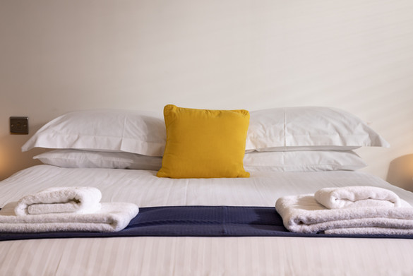 Bed made up with crisp linen and accent cushion