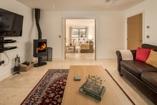Living room with woodburner and large sofa