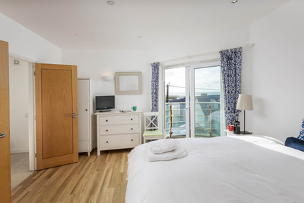 A spacious double bedroom with white linen
