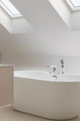 Freestanding bath in bathroom with skylight
