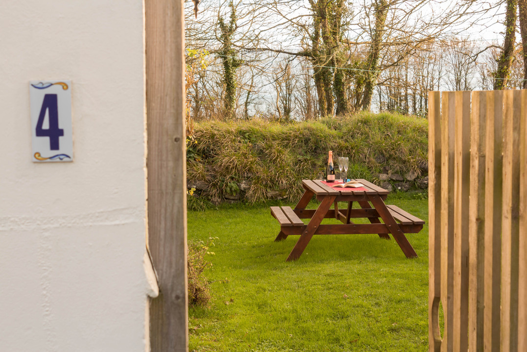 Enjoying a glass of bubbly in the garden of Cottage 4 at Little Gwendreath.