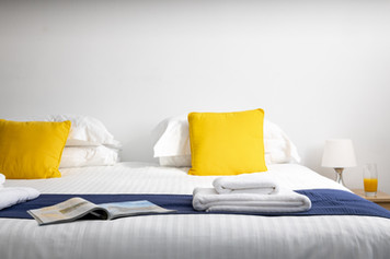Bed made up with linens and folded towels