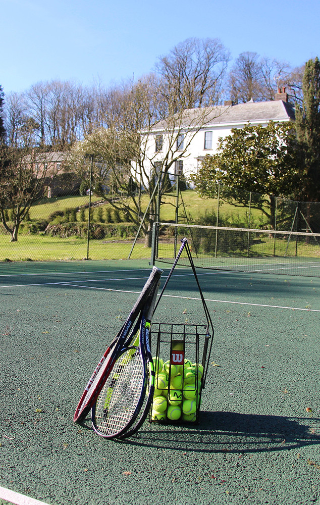 Play in the enclosed tennis court