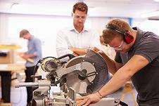rapaz a trabalhar numa máquina de corte com supervisão do professor