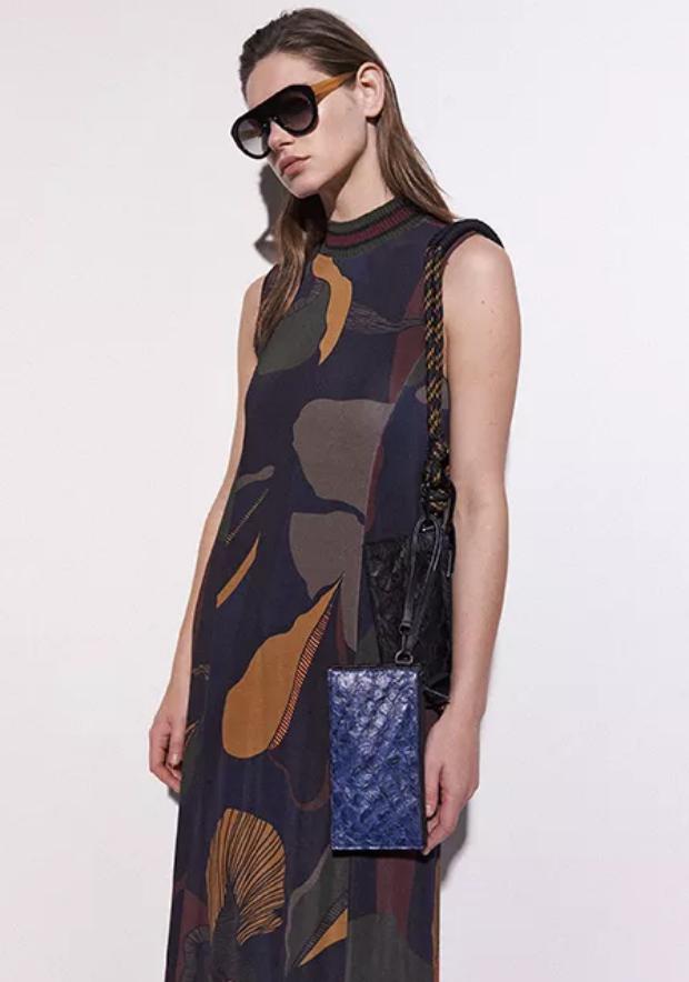 Modelo usando uma bolsa feita de pele de peixe pirarucu