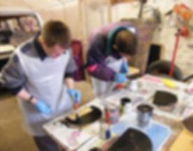 2 men painting wood in a workshop