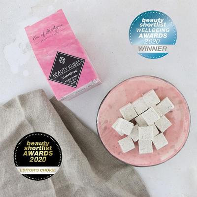 Image of the full size cardboard packaging in pink with beauty kubes in a bowl beside it