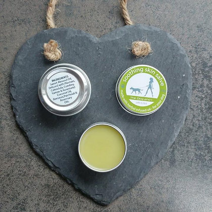 Open tin of soothing balm for dogs on a heart shaped slate next to an image of the underside of the tin