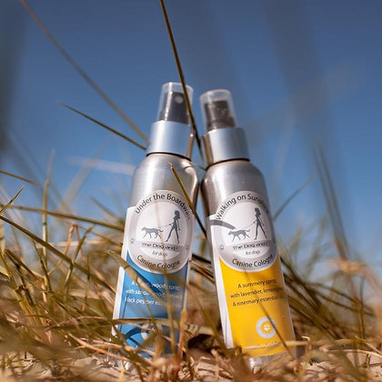 Canine Colognes in yellow and blue aluminium bottles on a grassy beach