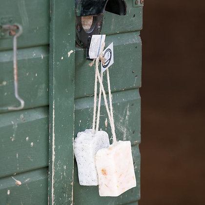 Bars of dog and horse shampoo hanging on a rope on a stable door