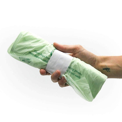 A rolled up bunch of caddy bags, held together in small cardboard wrapper being held in a hand