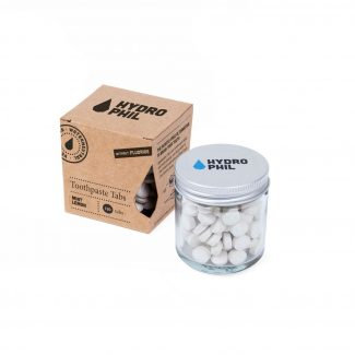 Toothpaste chewable toothpaste tabs in glass jar with aluminium lid next to cardboard packaging