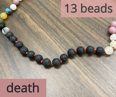 The thirteen black lava beads that appear in four sections. They represent the tarot card death.