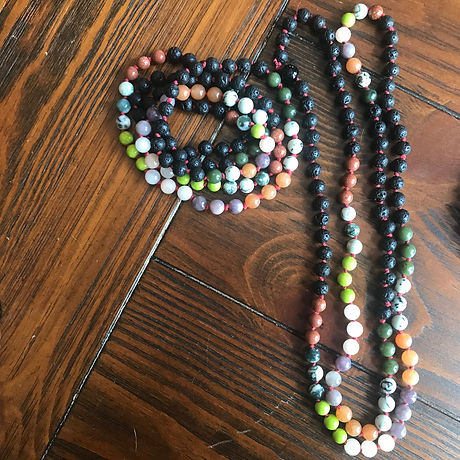 A pair of grief beads laying on top of a dark wood table. One set of beads is coiled up.
