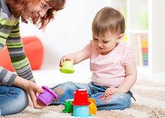 toddler and adult playing with color stacks