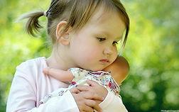 toddler cuddling baby doll
