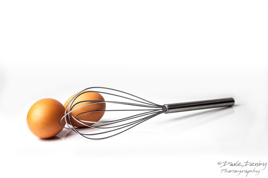 Eggs and Whisk on White Background