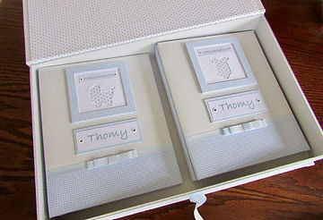 Kit contendo 2 álbuns com folhas plásticas para 50 fotos 15 X 21 cada, nos temas nascimento e mesversário, e uma caixa tipo livro feita em cartonagem para os 2 álbuns. Cada folha tem capacidade para 2 fotos. Capas revestidas com tecido, com plaquinha com nome do bebê e moldura decorada com carrinho de bebê e body, ambos em tecido.  É possível fazer em outras cores e estampas, de acordo com a disponibilidade.   Frete não incluído. Medidas dos álbuns: 24,0 x 19,0 x 3,5 cm (C x L x A) Medidas dacaixa: 42,0 x 26,5 x 6,0 cm (C x L x A) Peso: 2.600g Prazo de produção: 20 dias corridos  Valor: R$ 450,00