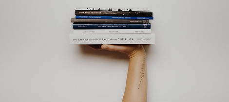 Woman%20with%20a%20tattoo%20holding%20up%20a%20stack%20of%20books._edited.jpg