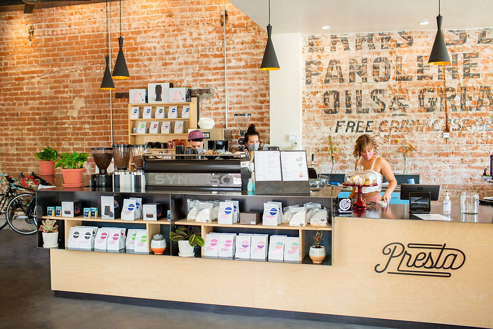 The coffee bar at Presta Coffee Roaster with employees making coffee behind the counter.