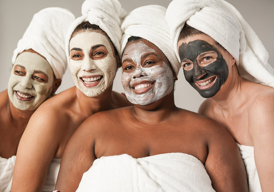Multiracial women enjoy spa day together with beauty face mask while wearing towels - Mult