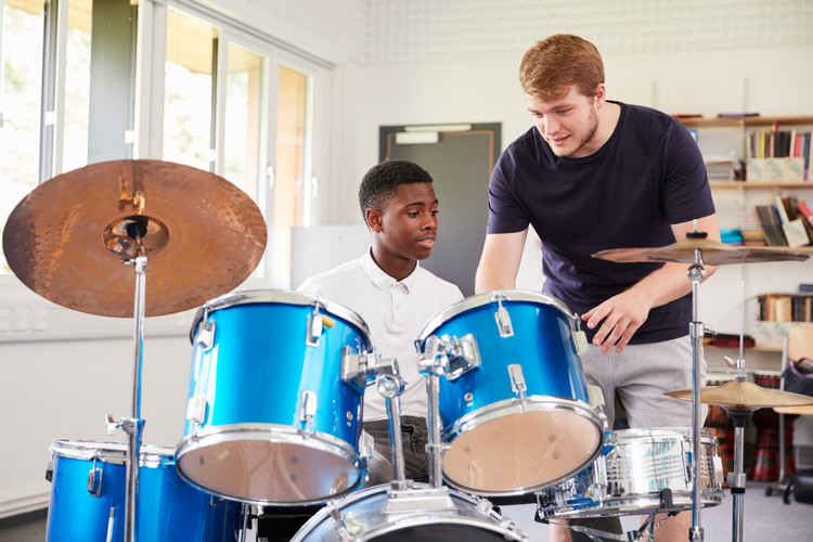 male-pupil-with-teacher-playing-drums-in