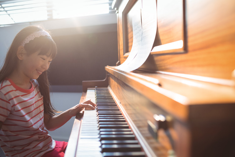 smiling-girl-practicing-piano-in-class-Z