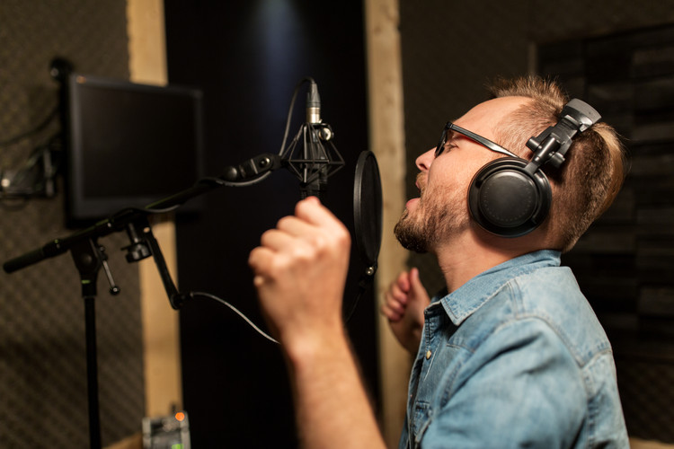 man-with-headphones-singing-at-recording