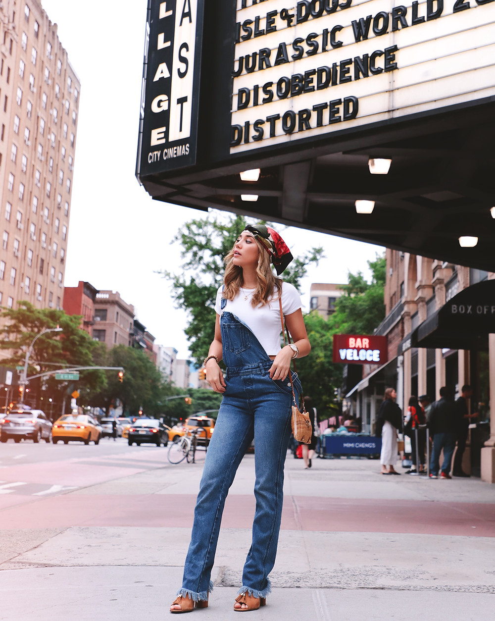 Fashion Blogger Barbie Brignoni wearing a denim overalls, white tee, tan mules and a head scarf. Standing in front of a theater in the Lower East Side, NYC.