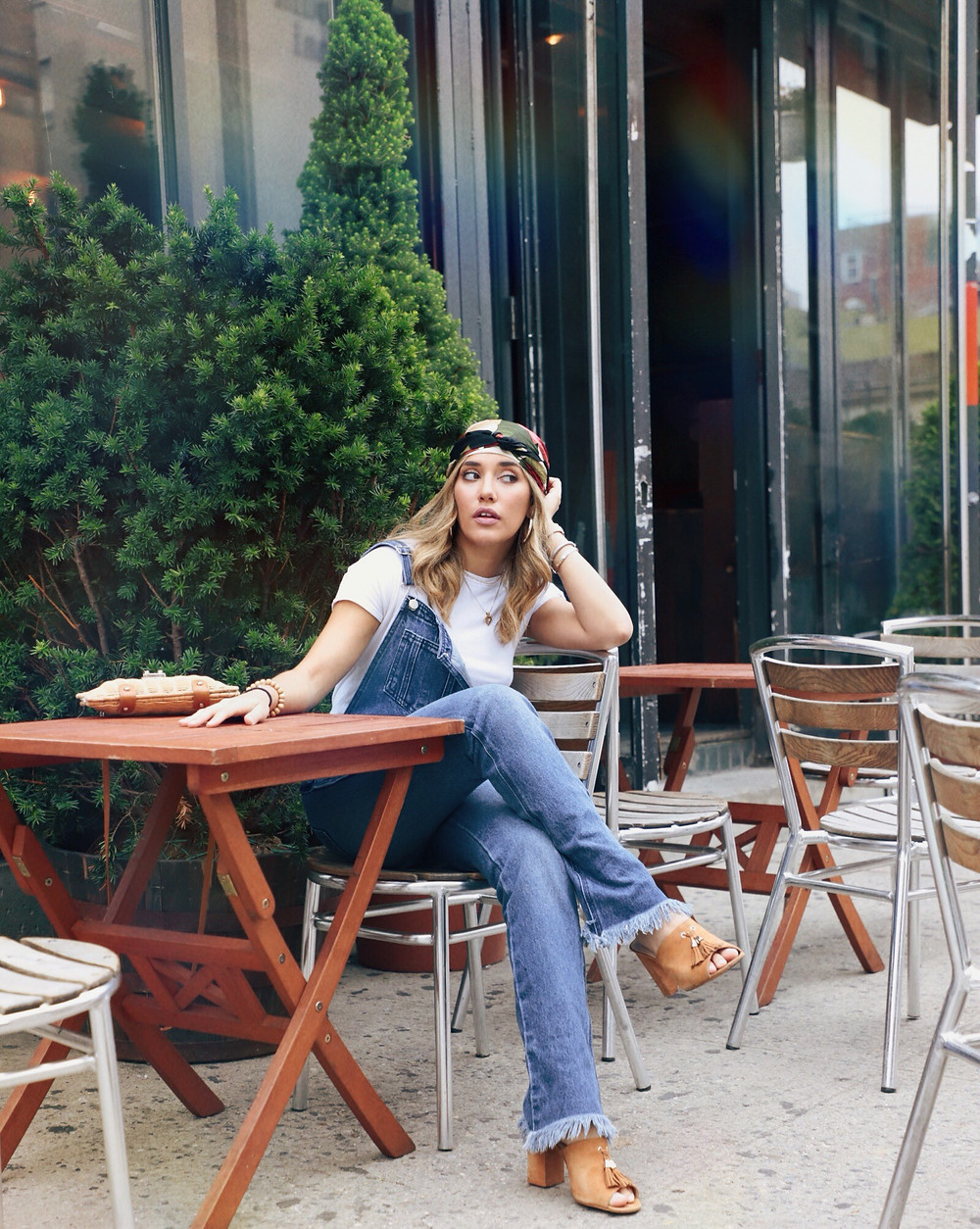 Fashion Blogger Barbie Brignoni wearing denim overalls and sitting outside in a Café in the Lower East Side