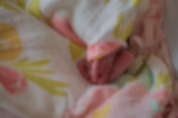 Sweet newborn baby toes crossed, cuddled up in a pastel pink and geen blanket
