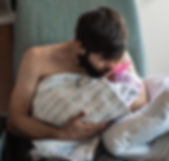 A new father holding his baby girl for the first time, skin to skin kangaroo care