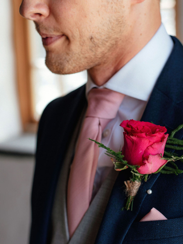 groomsman with pink flower