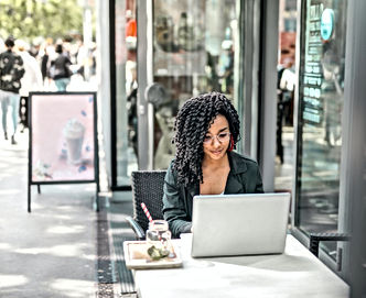 ethnic-young-woman-using-laptop-while-ha