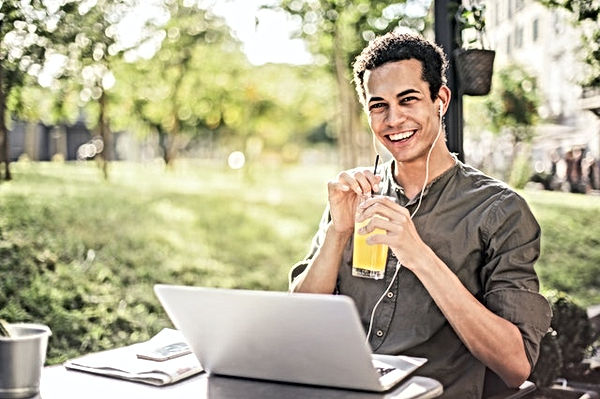 happy-man-sitting-with-laptop-and-juice-