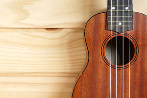ukulele-on-wooden-background-87661249.jpg
