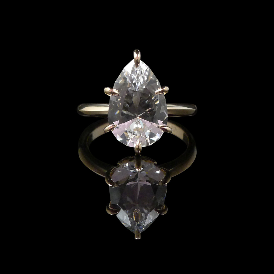 Engagement ring: 18 carat rose gold engagement ring featuring a pear-shaped white sapphire.