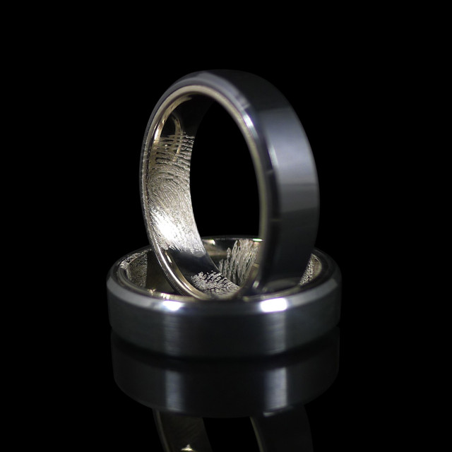 Custom designed and made black zirconium and 18ct white gold wedding rings, with finger prints engraved.