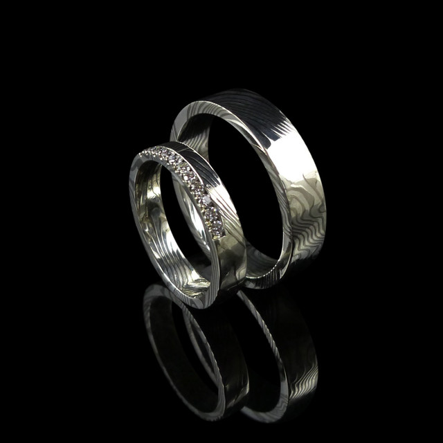Matching mokume gane wedding rings made in 14ct white gold and silver. Hers diamond set.  Mokume Gane is a metal working method that gives the metal a similar finish to the patterns in wood. This process uses a combination of different metals.