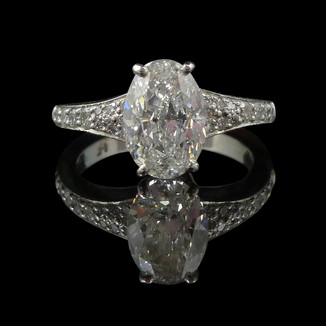 Engagement ring: Platinum engagement ring featuring a 2-carat oval-shaped diamond.
