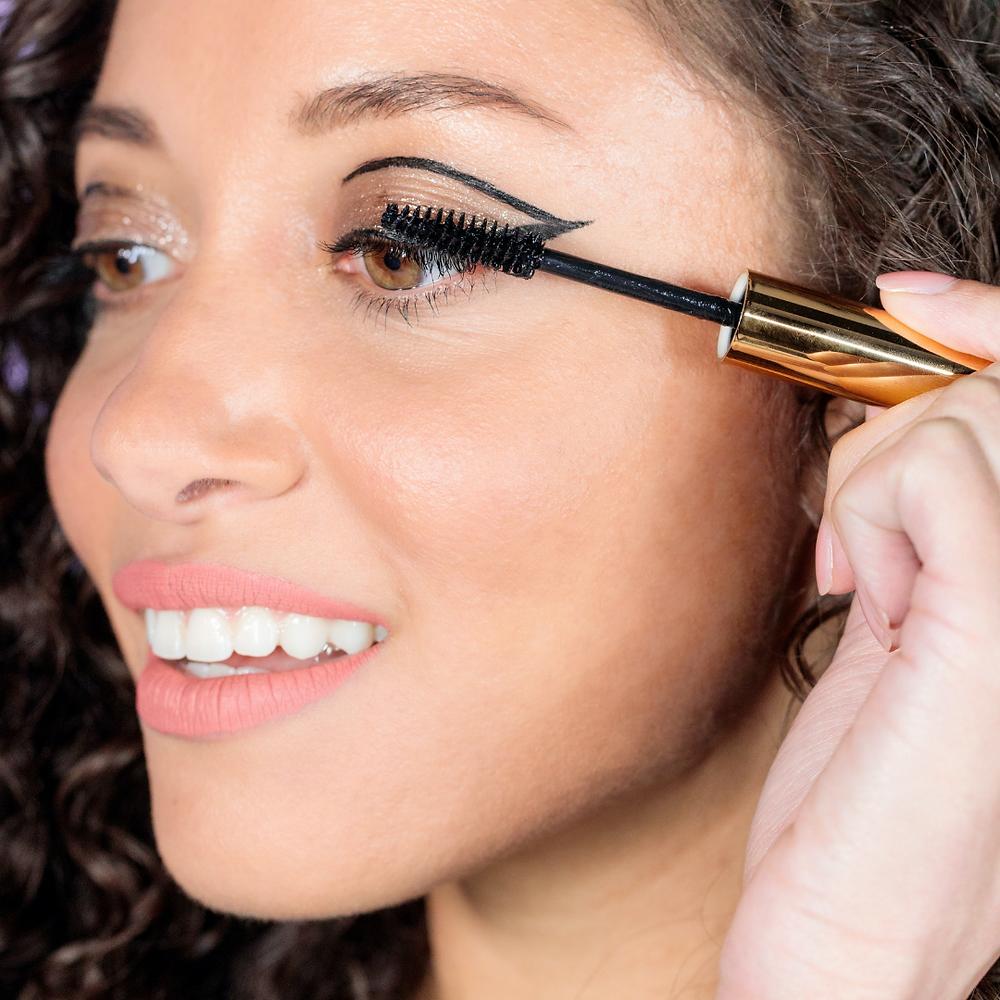 Mulher de cabelos cacheadosse maquiando usando um pincel de máscara para cílios em olhos castanhos claros com delineador vazado e sombra glitter