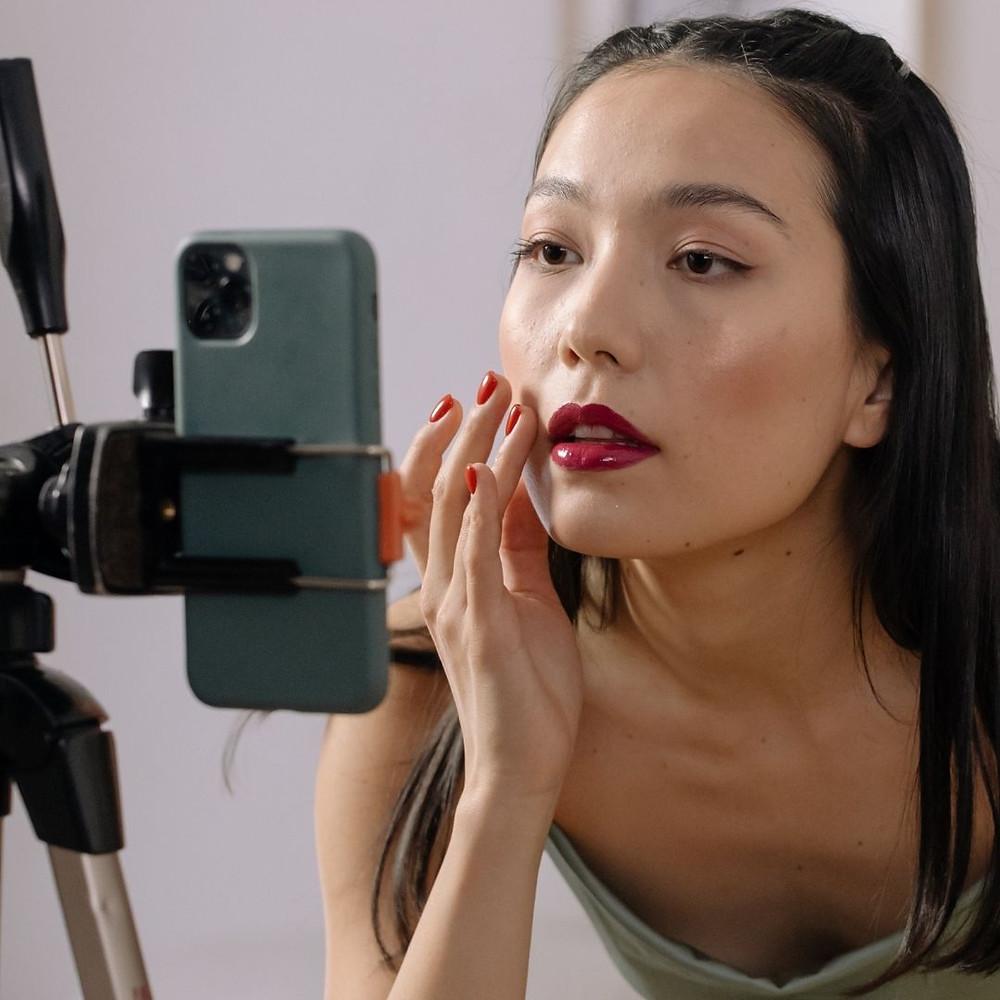 Mulher asiática retoca maquiagem se olhando no celular utilizando aplicativo como espelho virtual