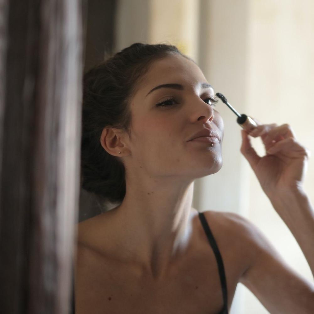 Mulher se maquiando em frente ao espelho com o queixo levantado