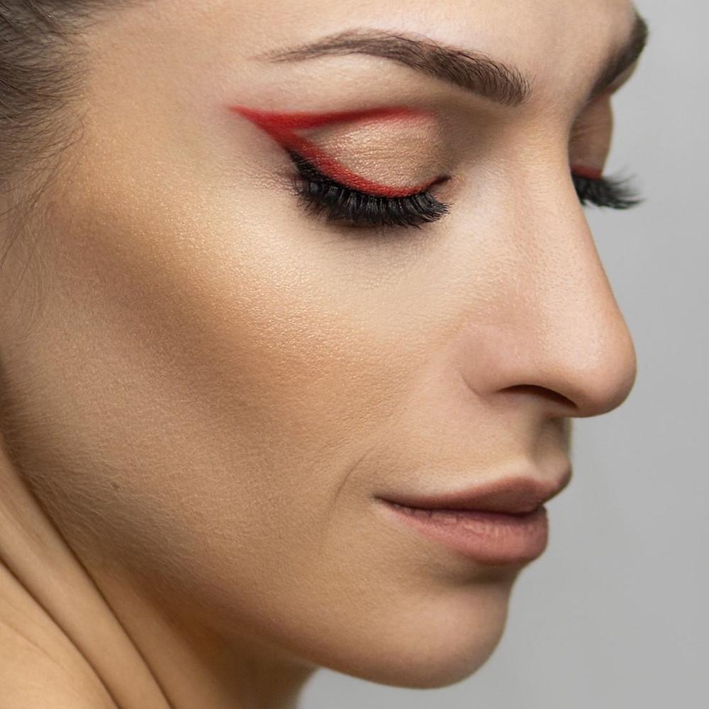 Mulher de perfil com os olhos fechados e make com delineado vermelho gráfico