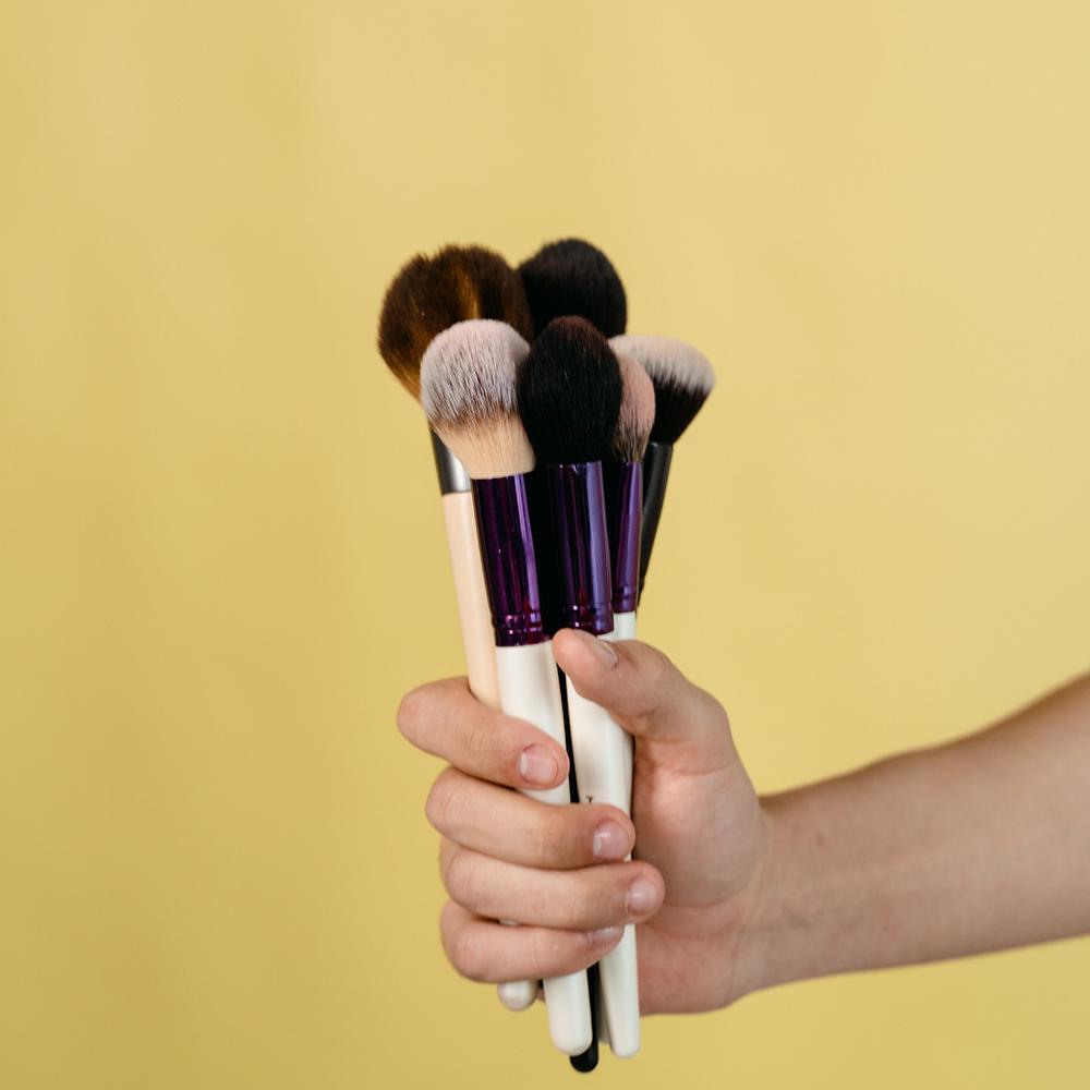 Mão segurando um conjunto de pincéis de maquiagem