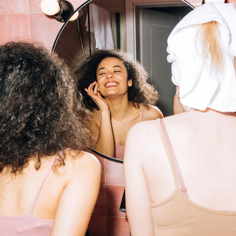 Garota de cabelos cacheados se olhando no espelho e sorrindo ao lado de amiga com toalha na cabeça